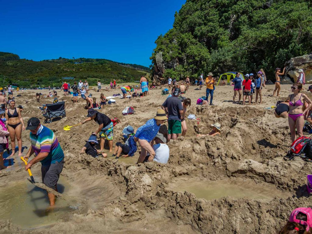 People digging holes at Hot Water Beach, Coromandel, North Island, New Zealand