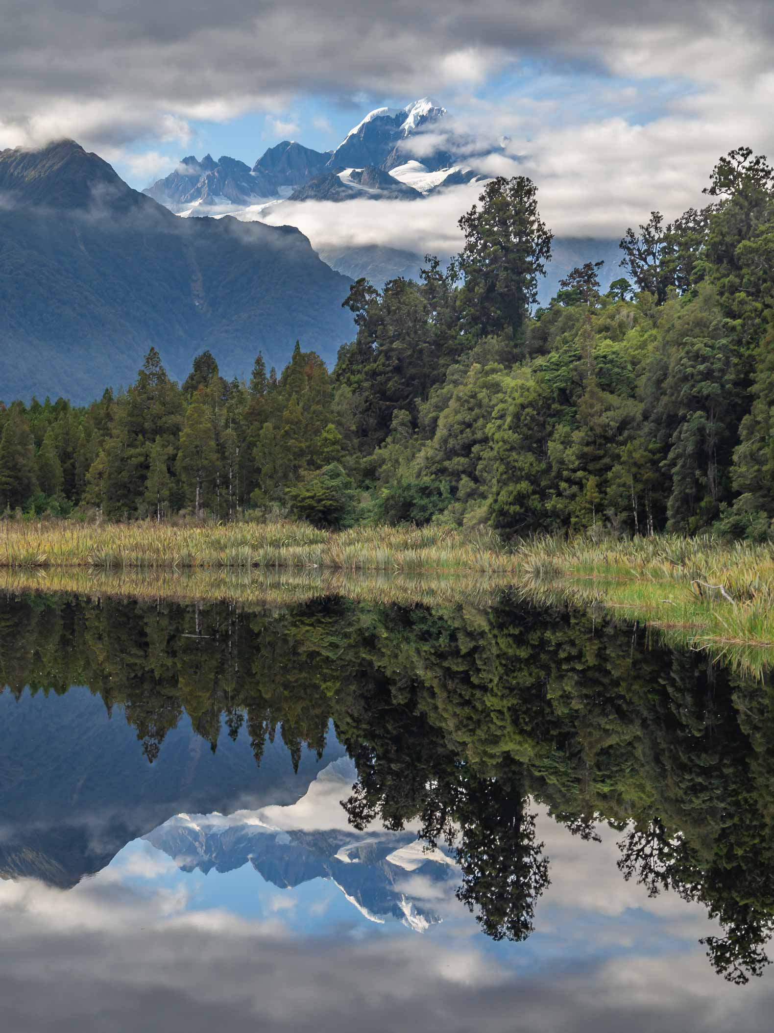 The image of Fox glacier reflected in Lake Mattheson, New Zealand.