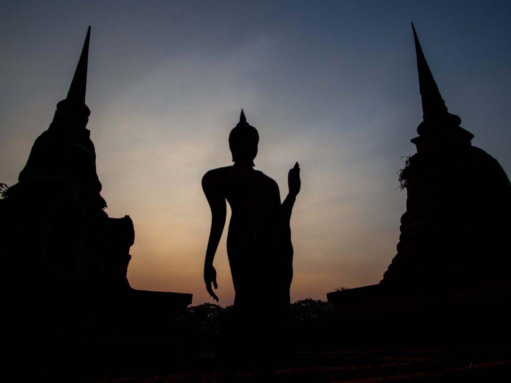 Buddha statue and stupas at sunset at Sukhothai historical park